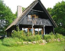 Sommerhuset i Båring Vig er i to etager med altan og stråtag