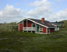 Det rødmalede sommerhus i Søndervig ligger på en kuperet naturgrund
